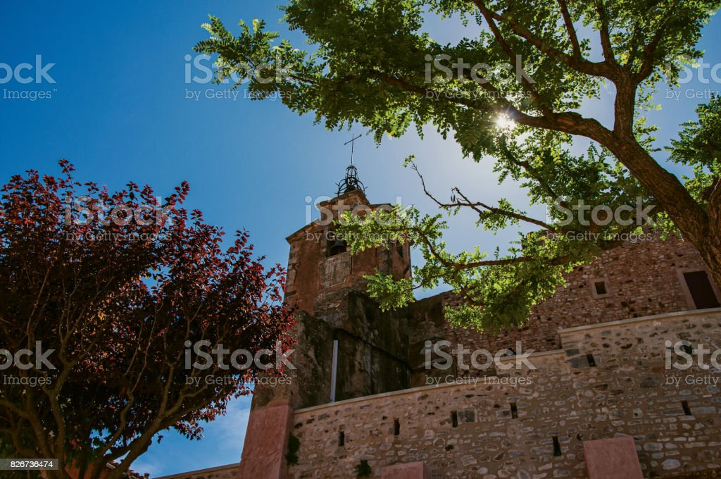 View of old church made of stone against the sunlight, in Roussillon. stock photo