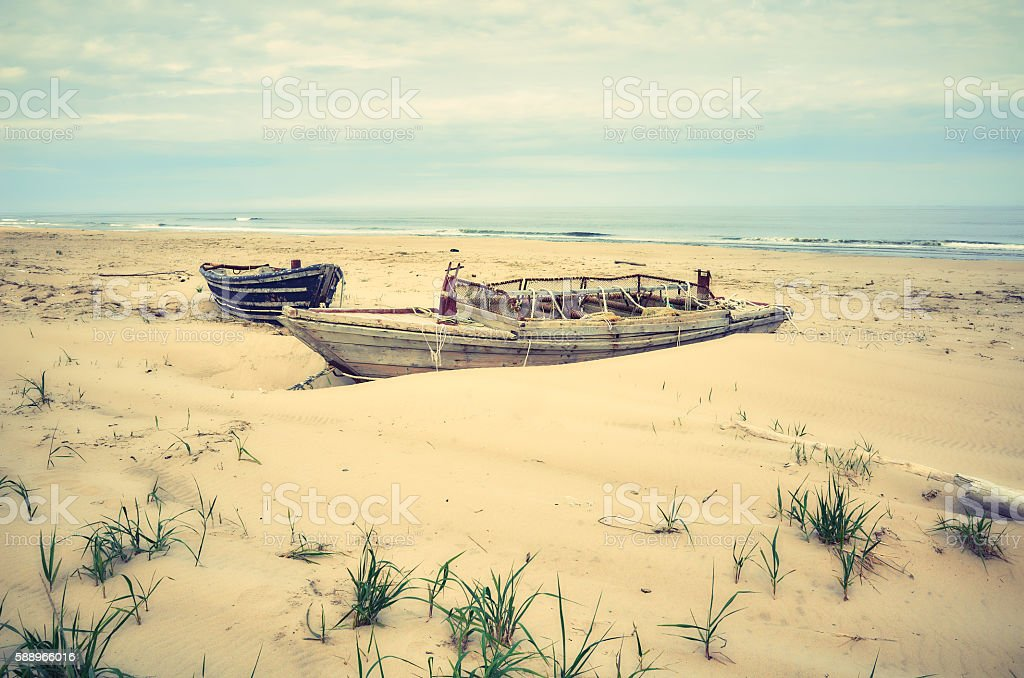 View of old lonely wooden boat on beach stock photo