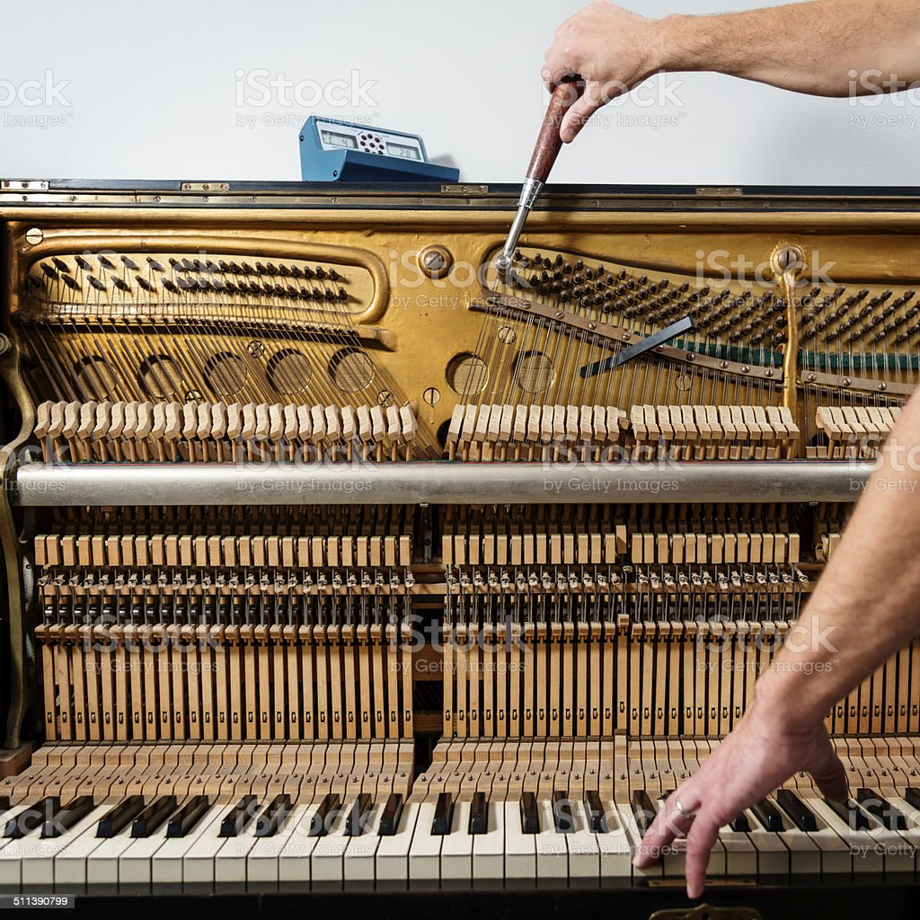 View of open piano while being tuned by piano tuner. stock photo