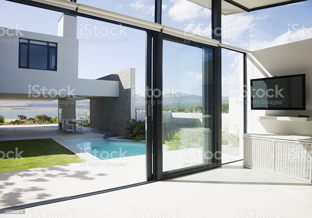 View of patio and swimming pool through sliding doors of modern house stock photo