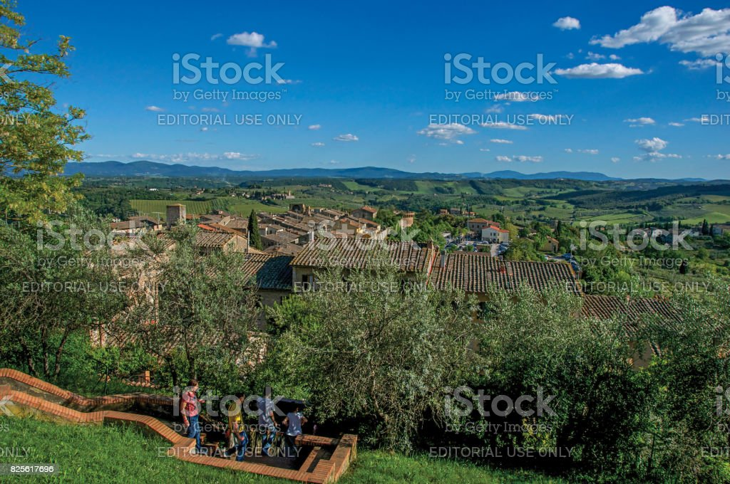 View of people descending staircase between trees at San Gimignano stock photo