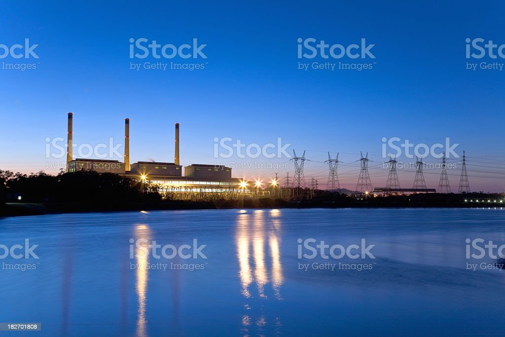 View of power station from a distance looking across a river royalty-free stock photo