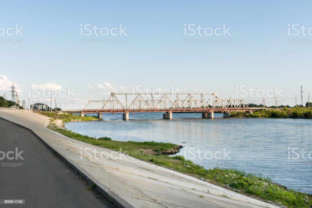 View of railway bridge across the Volga river from pedestrian embankment in Syzran, Russia. stock photo