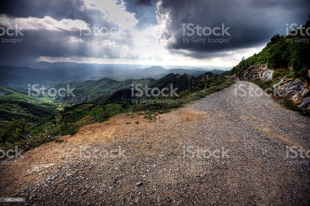 View of road through green mountains on a cloudy day royalty-free stock photo