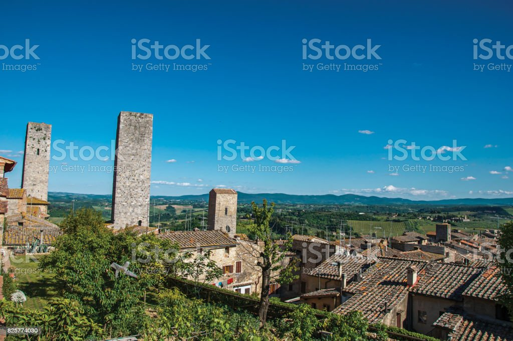 View of rooftops and towers with green hills in the background at San Gimignano. stock photo