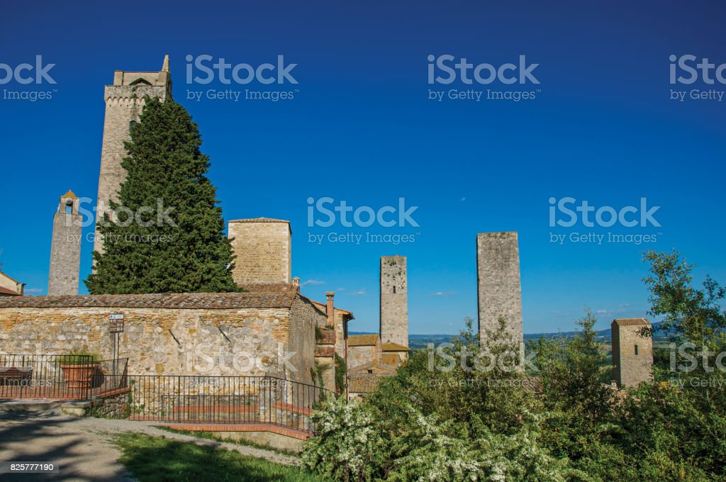 View of rooftops and towers with trees and blue sunny sky at San Gimignano. stock photo