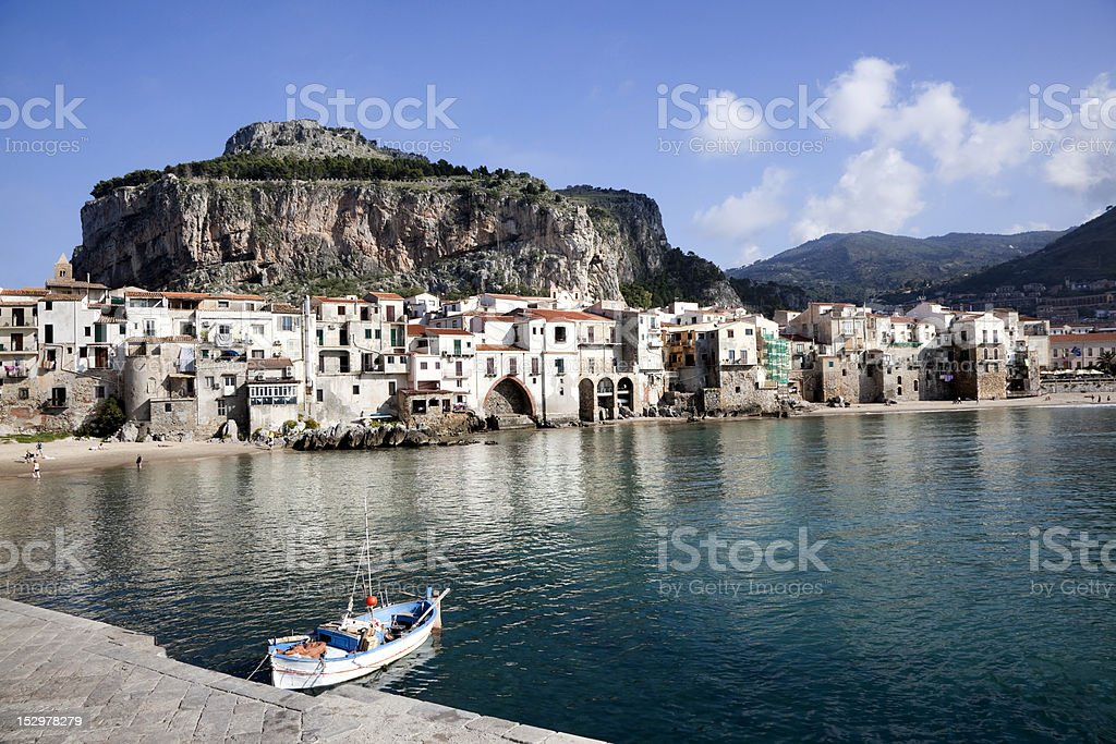 View of Rowboat, Old Buildings and Mountain at Cefalu Beach stock photo