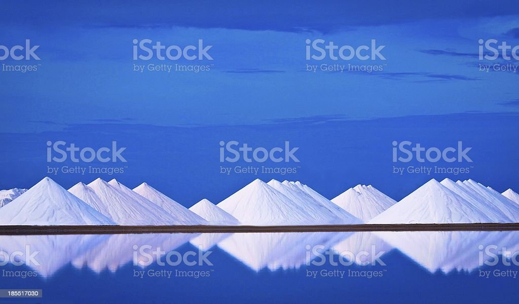 View of salt mines reflecting off water with blue sky stock photo