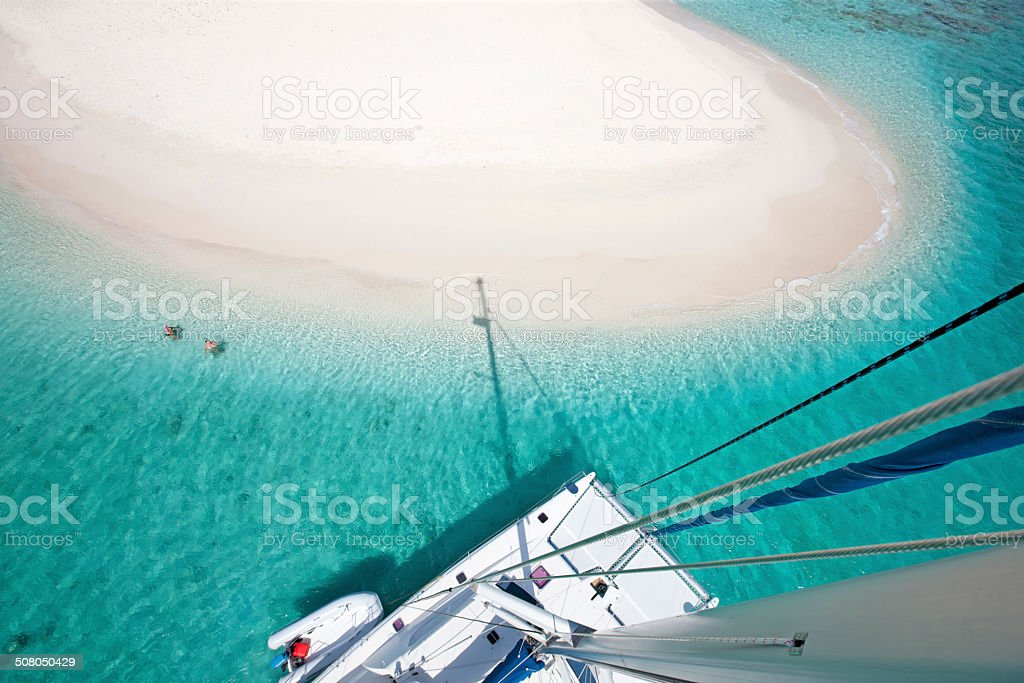 view of Sandy Spit, BVI from the catamaran's mast stock photo