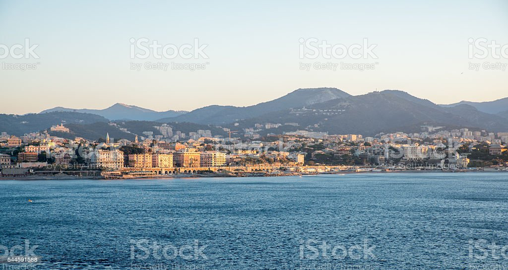 View of sea in front of city against mountains stock photo