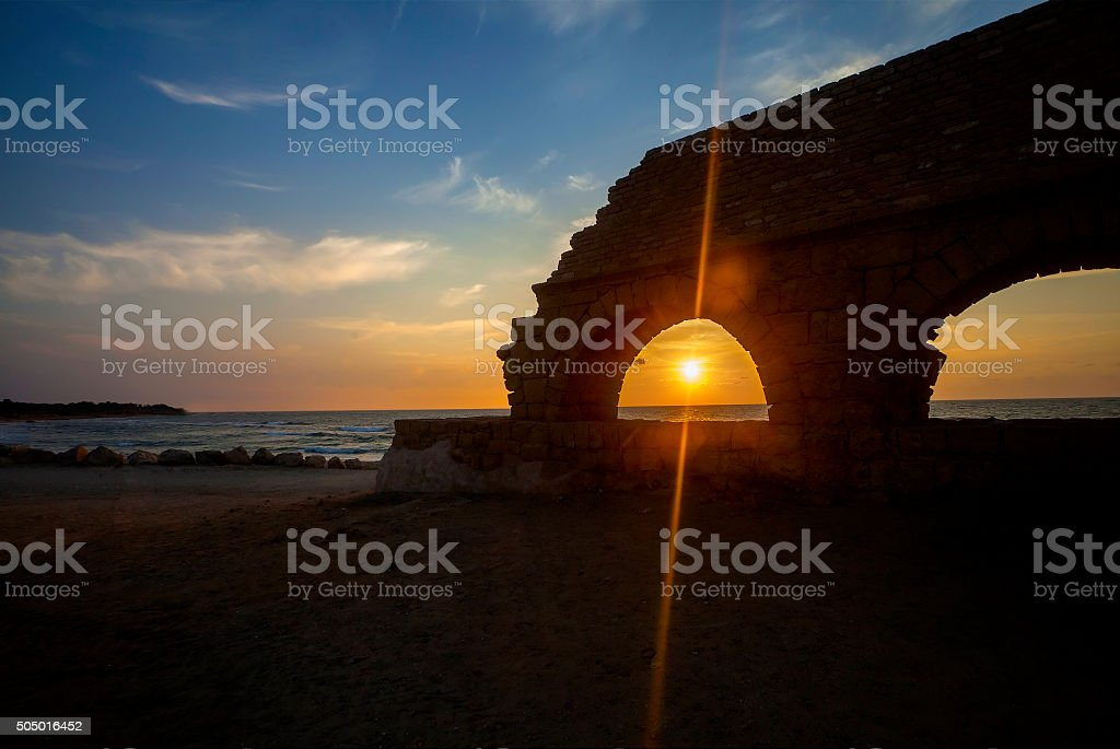 View of sinking sun through aqueduct arch stock photo