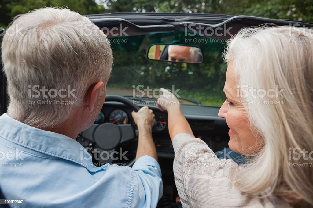 View of smiling mature couple going for a ride together stock photo