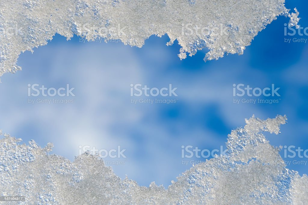 View of snow through a window or roof light and blue sky stock photo