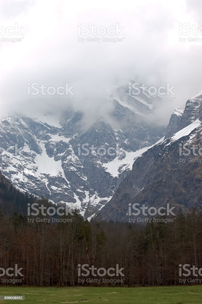 View of snow-covered mountains in clouds. stock photo
