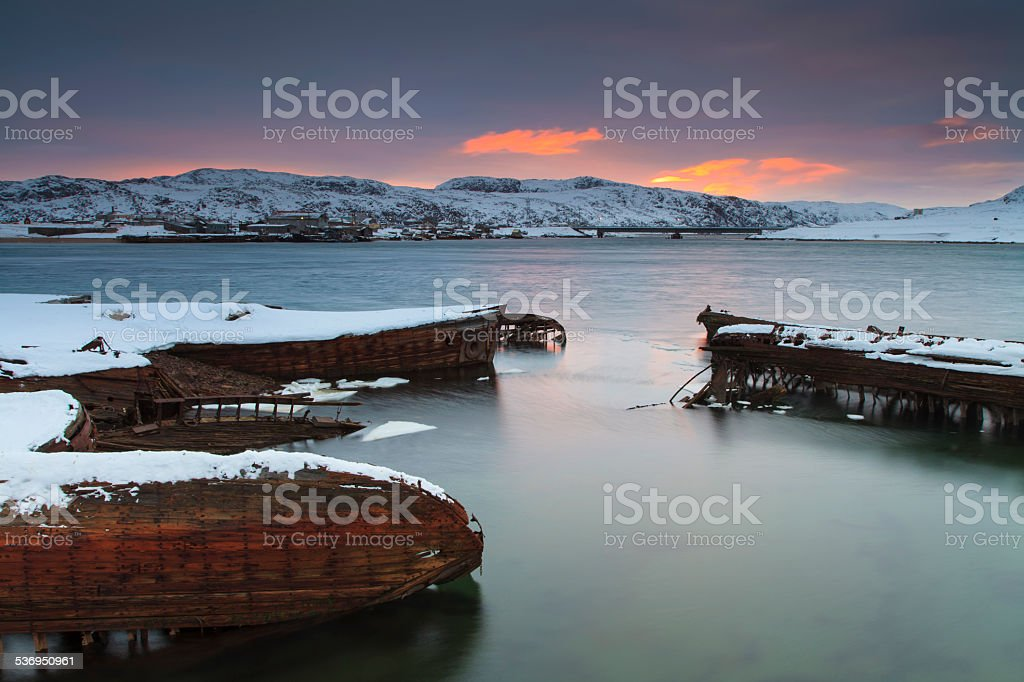View of snow-covered shore with old boats stock photo