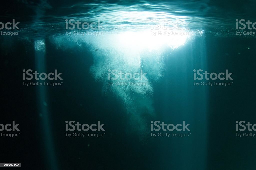 view of splash of entering water by diver lots of bubbles and blue laser beams of light stock photo
