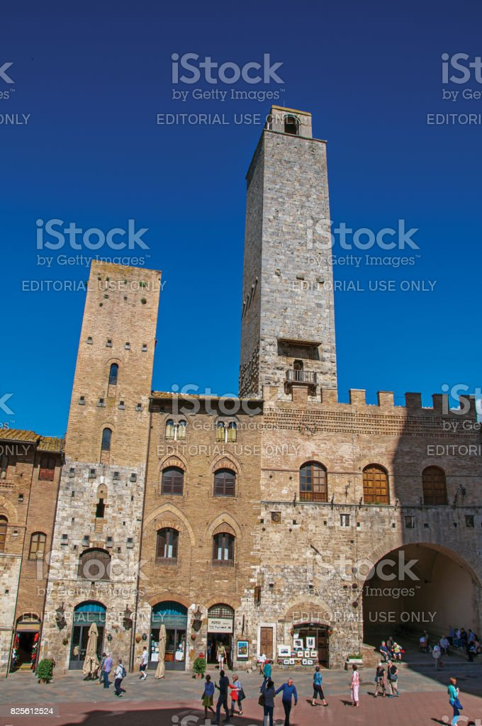 View of square with people, old building and tower in San Gimignano stock photo