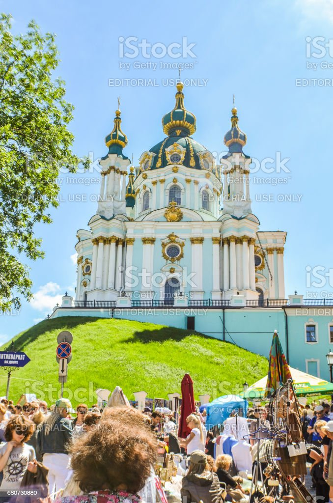 View of St Andrew's Church on a hill called Andriyivskyy Descent with many tourists stock photo