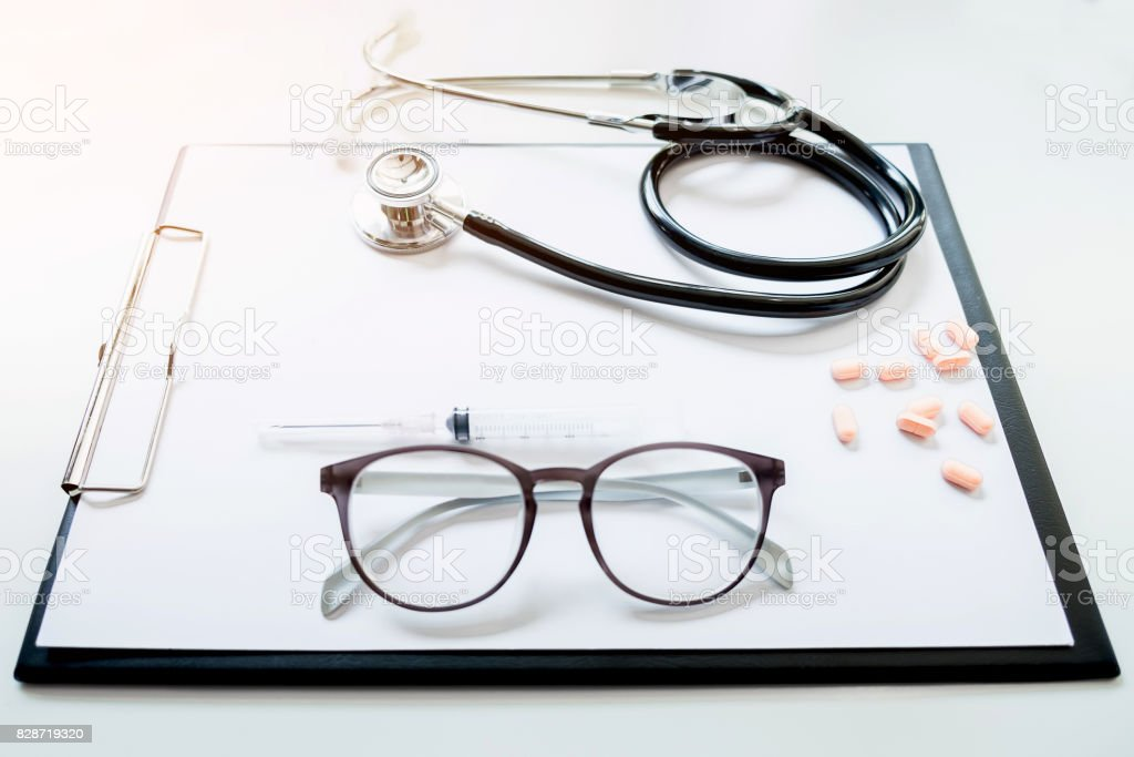View of stethoscope and equipment on foreground table stock photo