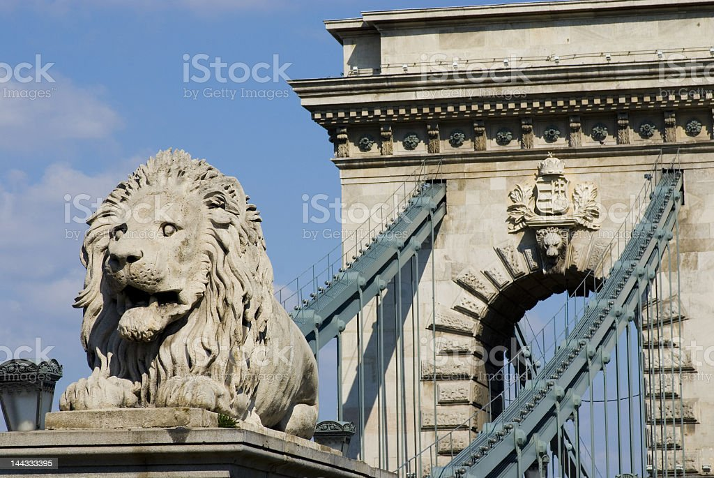 View of stone arch and chain bridge with lion statue stock photo