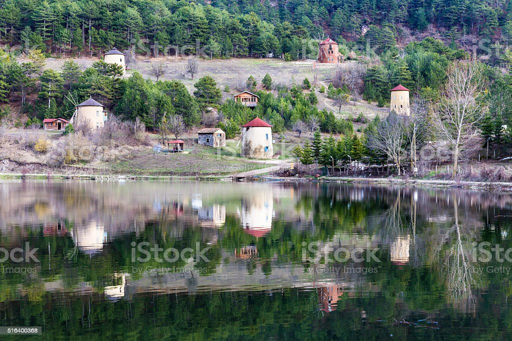View of stone windmills and forest reflection on Cubuk Lake stock photo