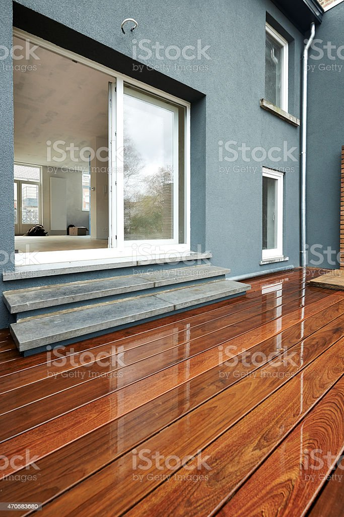 View of the back of a house with wooden decking and doors stock photo