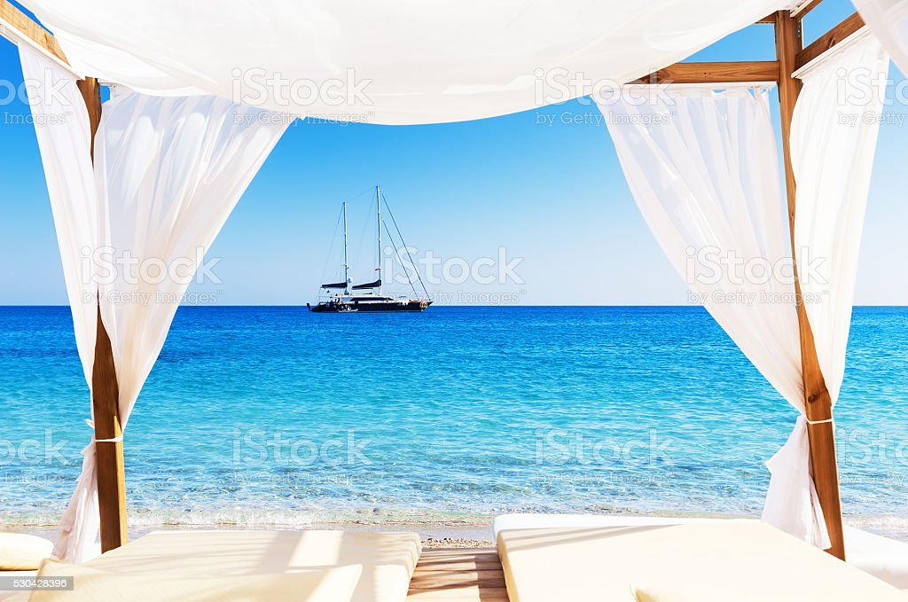 View of the beautiful beach through a Balinese bed stock photo