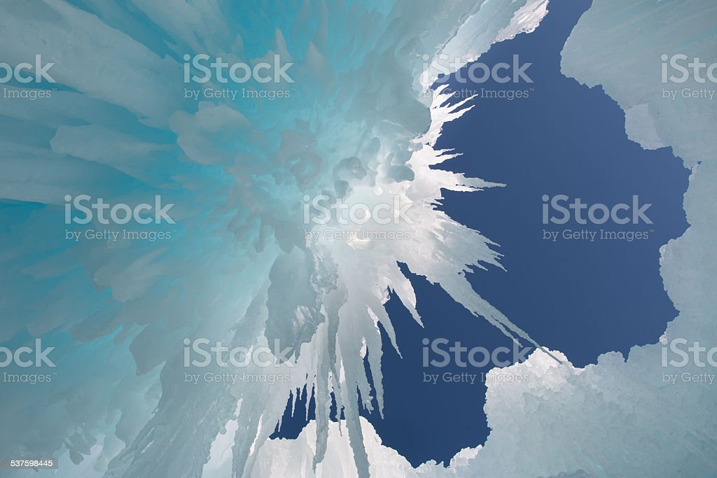 View of the blue sky through the hanging icicles stock photo