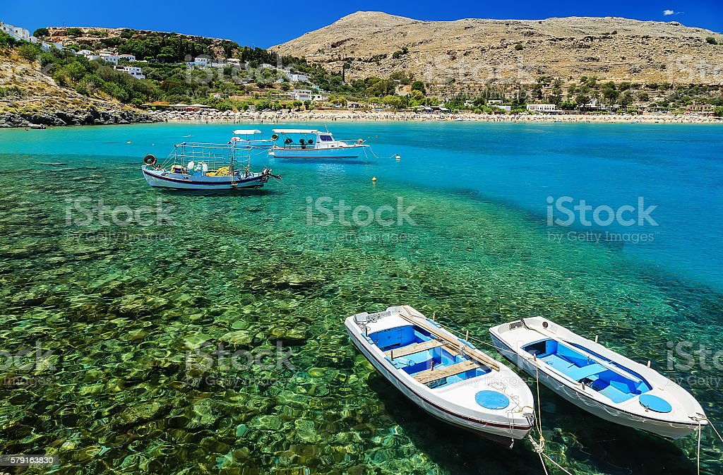 view of the coast with boats in Lindos bay, Greece stock photo