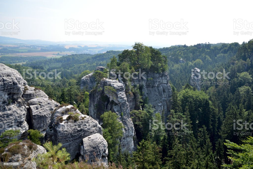 View of the high rock surrounded by a dense forest under a blue sky in the Czech Paradise in Czech Republic stock photo