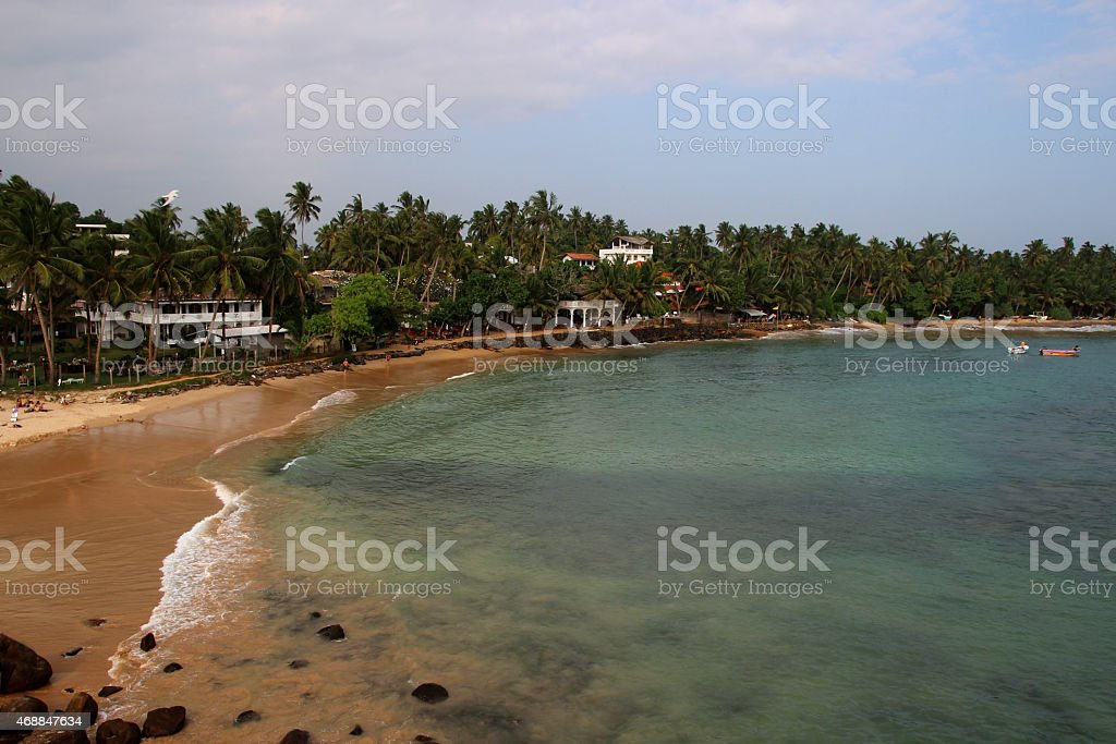 view of the ocean and sandy seashore with palm trees royalty-free stock photo