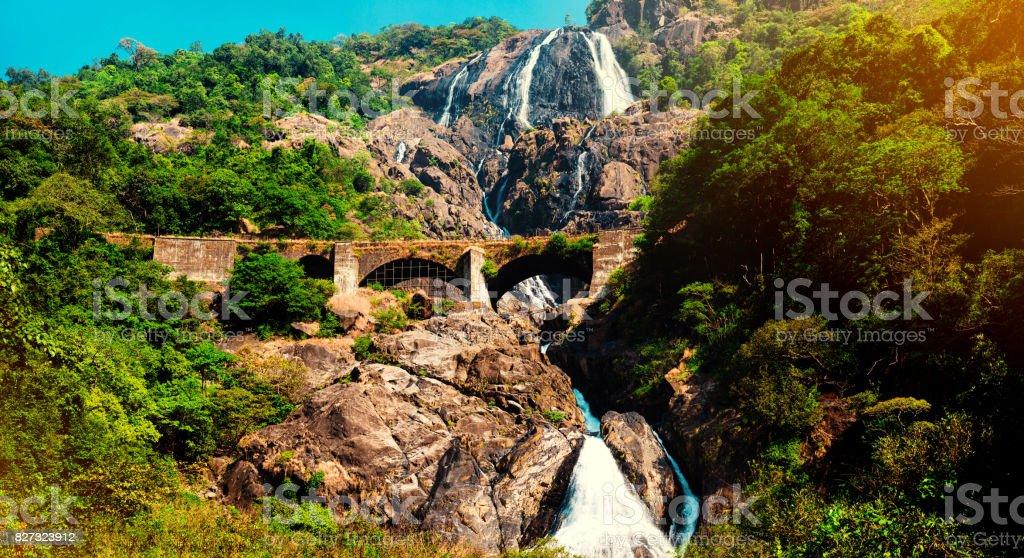 View of the railway bridge in the mountains through the waterfall, India, Goa stock photo