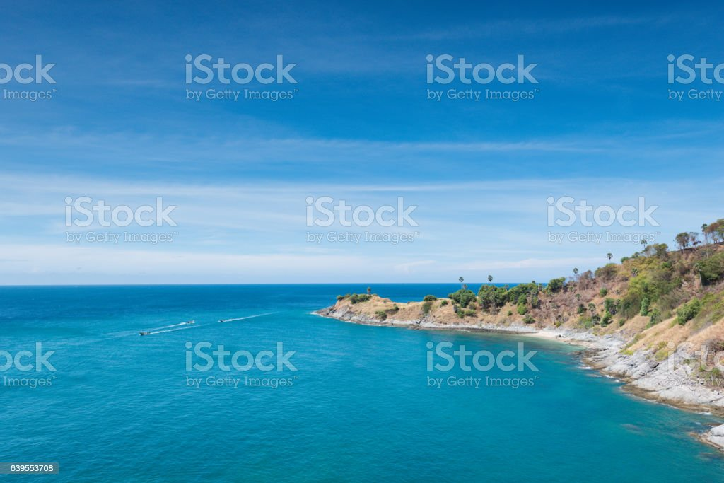 View of the rocky cliffs boat sailboat and clear sea stock photo