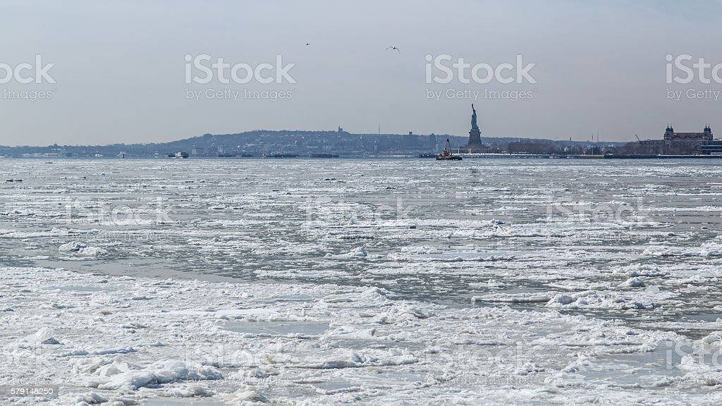 View of the Statue of Liberty across frozen Hudson River stock photo