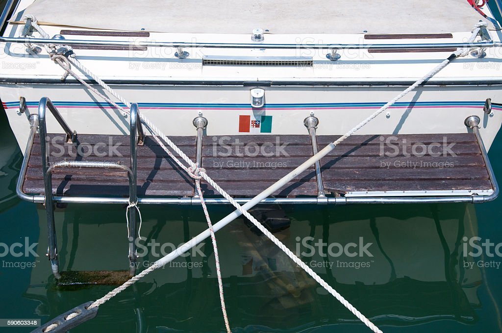 view of the stern of a white boat docked stock photo