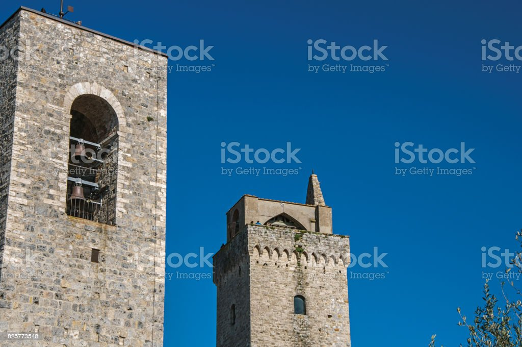 View of the stone towers with bells on the sunny blue sky at San Gimignano. stock photo
