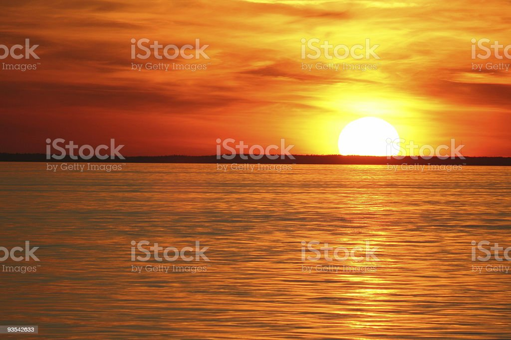View of the sun setting over the ocean stock photo