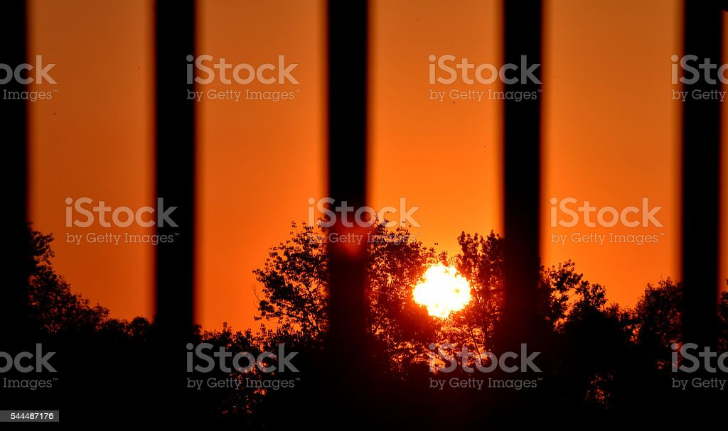 view of the sunset through the bars stock photo