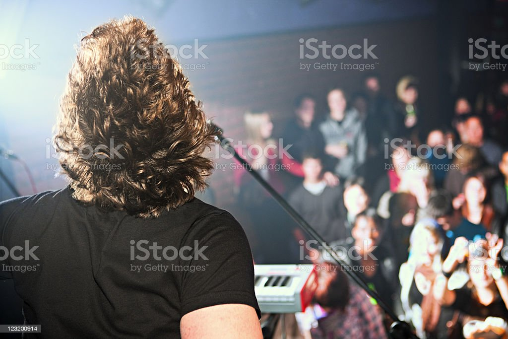 View of thrilled audience over rock musician's shoulder royalty-free stock photo