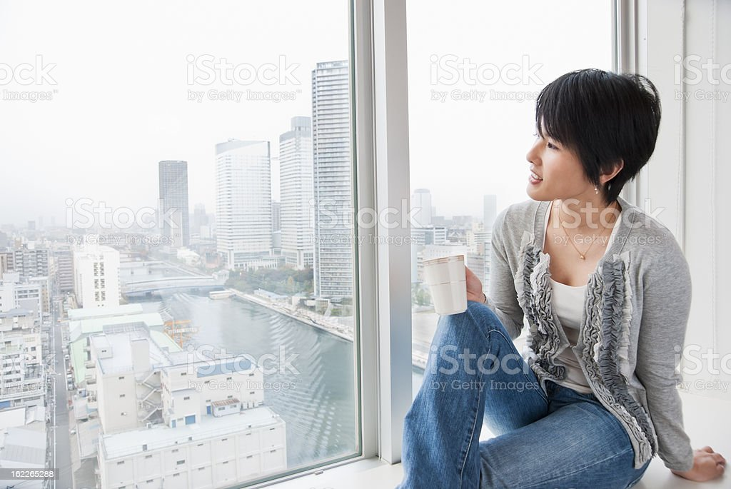 View of Tokyo Bay area from window - Asian woman stock photo