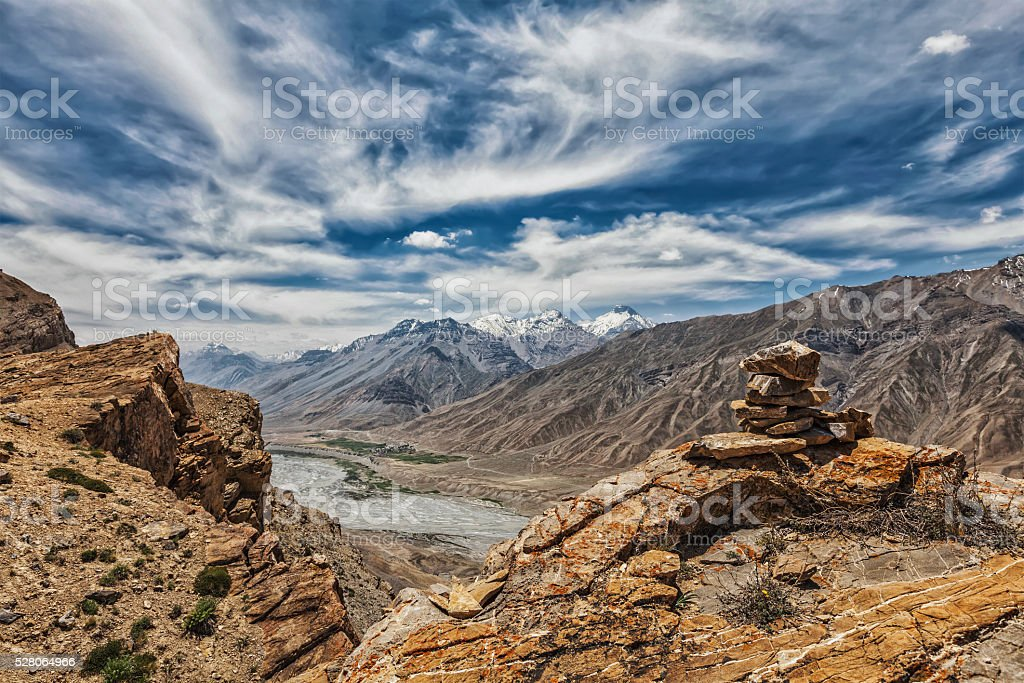 View of valley in Himalayas with stone cairn on cliff stock photo