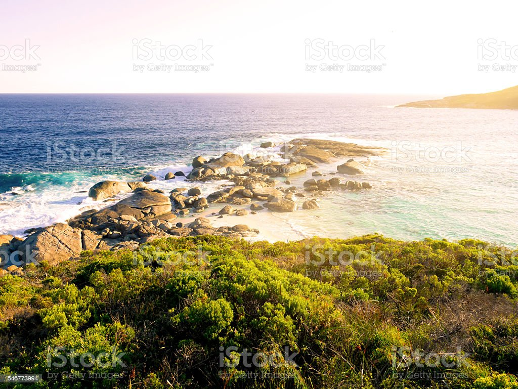 View of wave crashing against rocks and sunset stock photo
