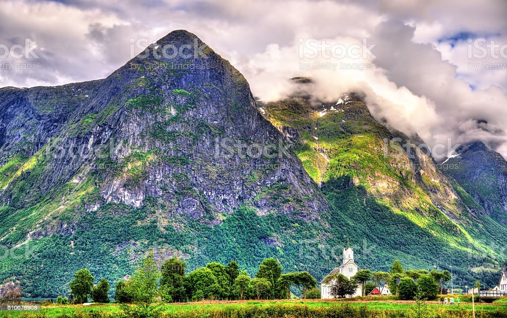 View of white wooden Oppstryn Church and mountains in Norway stock photo
