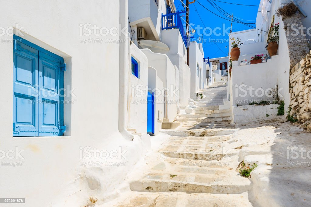 A view of whitewashed street with blue windows and doors in beautiful Mykonos town, Cyclades islands, Greece stock photo