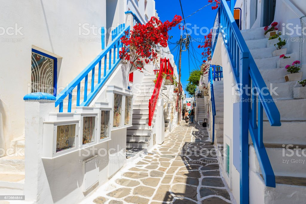 A view of whitewashed street with blue windows and flowers in beautiful Mykonos town, Cyclades islands, Greece stock photo