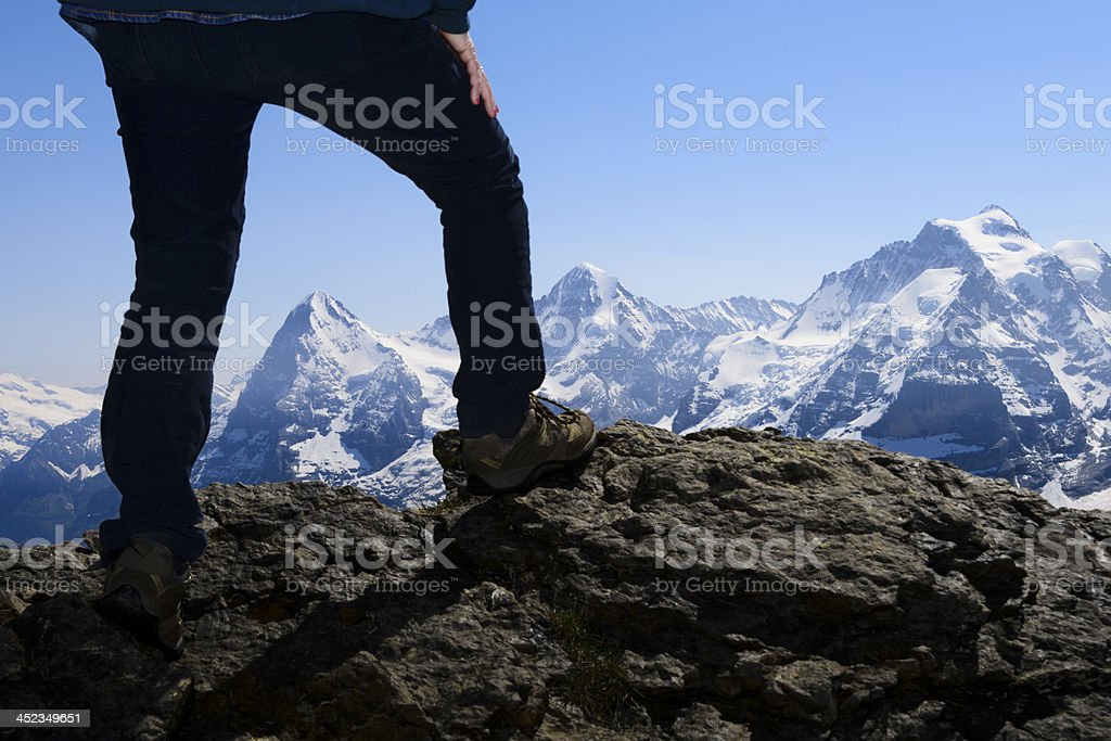 View of woman hiker's legs as she admires mountain peaks royalty-free stock photo