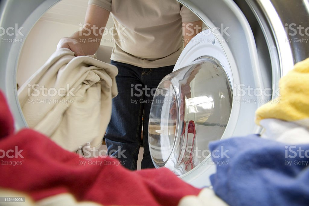 View of woman loading clothes into a washing machine stock photo