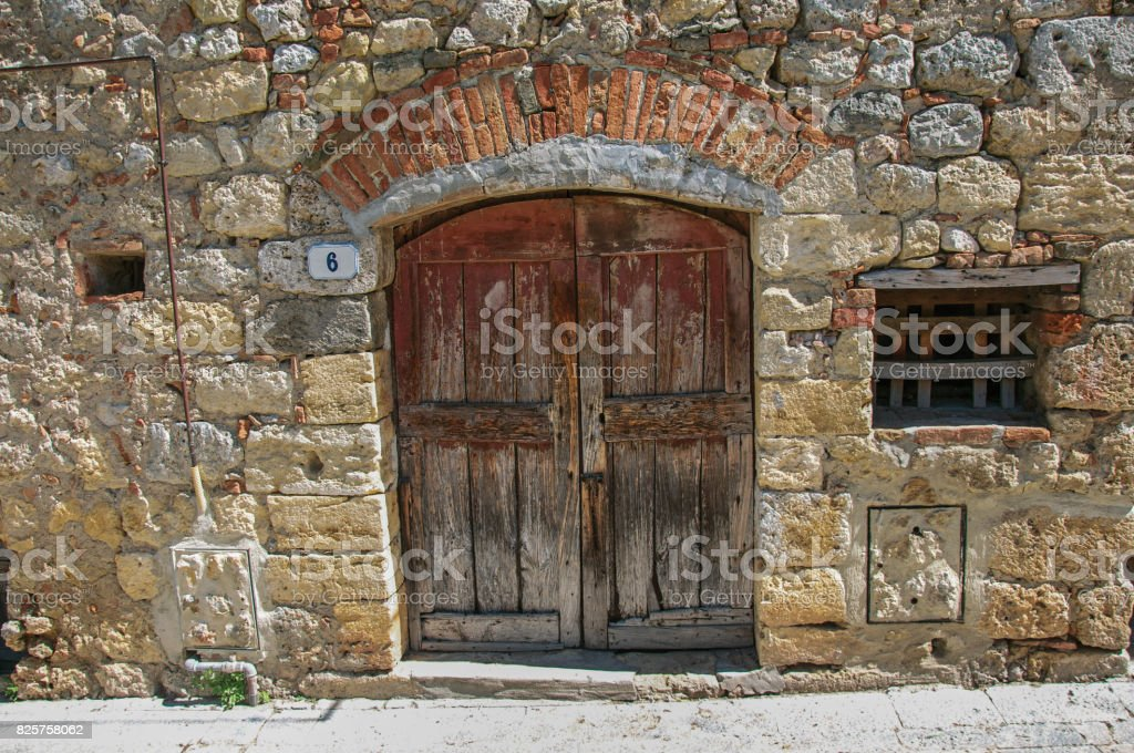 View of wooden door in a stone wall in the hamlet of Monteriggioni. stock photo
