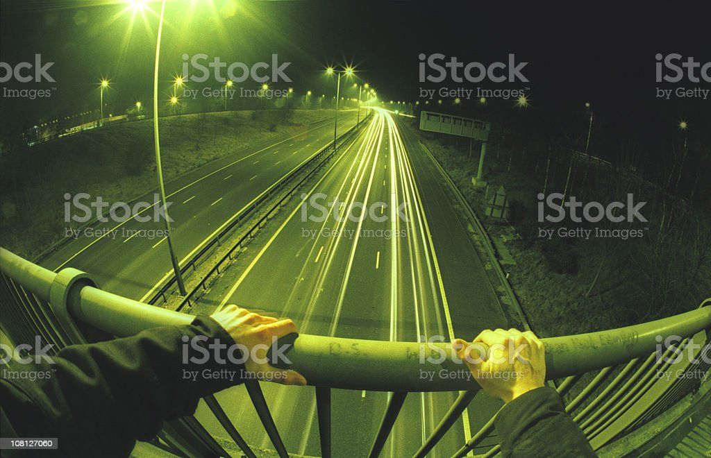 View off a freeway bridge with hands on railings royalty-free stock photo