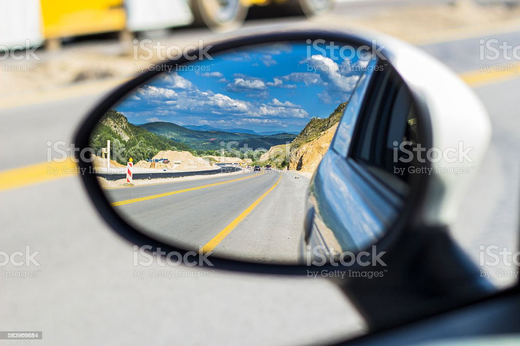 View on asphalt road highway from car mirror. stock photo